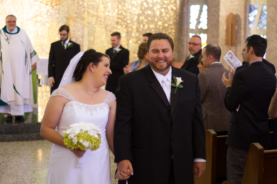 Bride and Groom walk happily out of the church