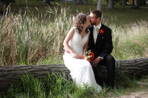 Bride and Groom Kiss on a Log