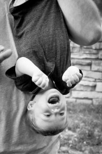 One year old boy hangs upside down with Dad